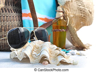 sunglasses, shells and beach bag - sunglasses resting on...