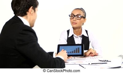 Discussion between a businessman and businesswoman. It shows the graphics tablet, developing a business project and analyzing market data information