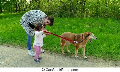 Mom And Daughter Smiling With Dog