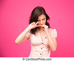 Young woman biting her nails over pink background Looking at...
