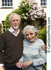 Retired Couple Standing Outside Pretty Home
