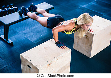 Beautiful sports woman doing push ups on fit box at gym