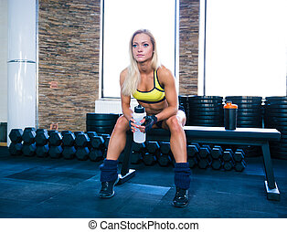 Beautiful sporty woman sitting on bench with bottle of water...