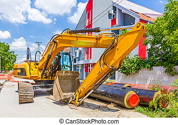 Yellow excavator at construction site in urban settlement