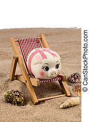 beach chair with piggy bank on the sandy beach. symbolic...