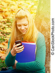 Beautiful blonde girl in nature with cell phone in park