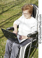 senior woman with computer outdoors