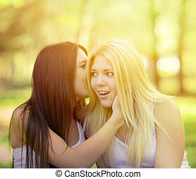 Two girl friends whispering secrets outdoors