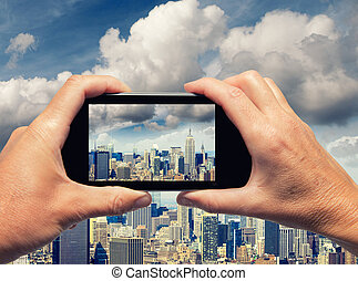 Man and woman hand capturing New York City skyline with...