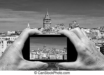 Man and woman hand capturing Beyoglu skyline skyline with...