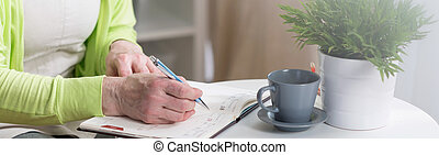 Writing in calendar - Close-up of female hands writing in...