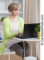Dating online on laptop - Attractive mature woman dating...