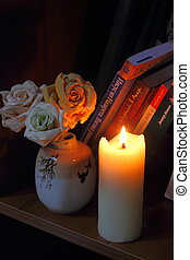 Candles and flowers - On the bookshelf are burning candle...