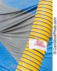 Blue and gray home fumigation tarp and yellow duct with...