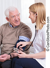 Nurse measuring blood pressure of senior man