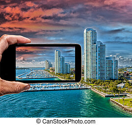 Male hand with smartphone taking a picture of Miami from...