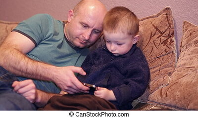 Little boy with his uncle watching a movie on phone