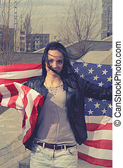 Younf black haired women with stars and stripes flag...