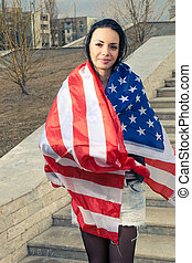 Younf latino women warped in US flag outdoors patritic...