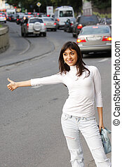 Hitchhiking brunette girl with traffic on background