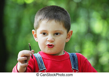 Concentration facial expression on little boy face outdoor...
