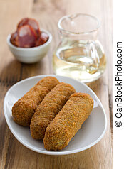 meat croquete on white dish and wine