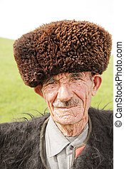 Old man in traditional clothes outdoor closeup portrait