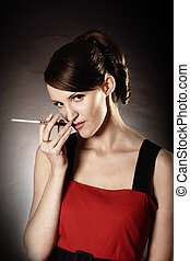 Inhalation - Smoking woman portrait over dark background