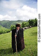 Herdsman in mountains - Elderly herdsman in summer mountains...