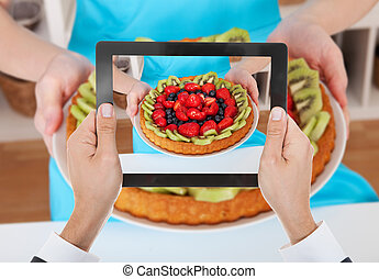 Person Hand Photographing Fruit Tart With Digital Tablet