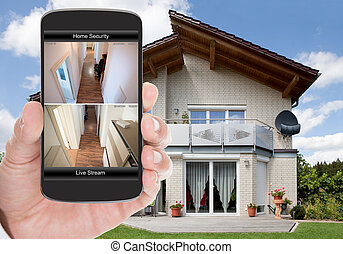 Home Security - Close-up Of Person Hand Holding Mobile Phone...