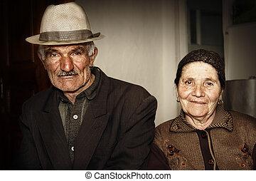 Elderly couple sitting in kitchen portrait