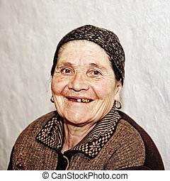 Smiling elderly woman with golden teeth sitting at light...