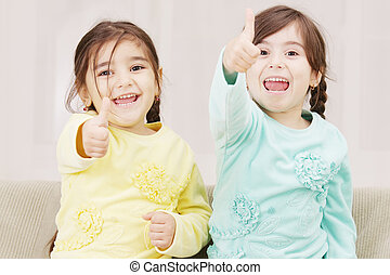 Happy sisters - Two happy little sisters raising thumb up...