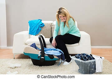 Post Natal Depression - Unhappy Mother With Laundry Clothes...