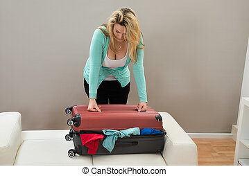 Woman Trying To Close The Suitcase