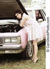 Car repair - Serious young woman in pink repairing retro car