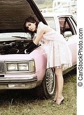 Car repair - Serious young woman in pink repairing retro car