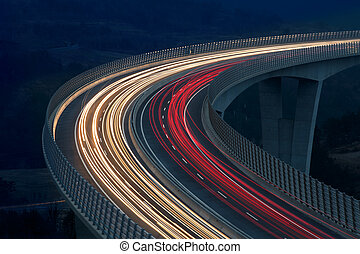 Blurred lights of vehicles driving on a tall viaduct with...