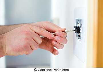 home renovation - Man installing light switch with...