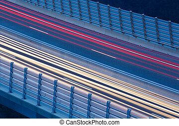Blurred lights of vehicles driving on a viaduct with wind...