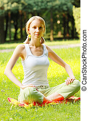 Blonde in park legs crossed - Pretty young blond woman...
