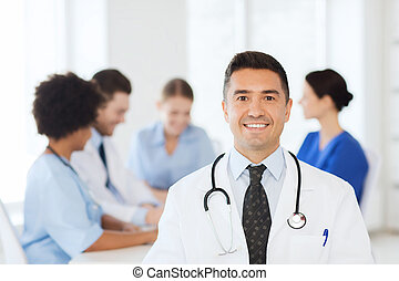 happy doctor over group of medics at hospital - clinic,...