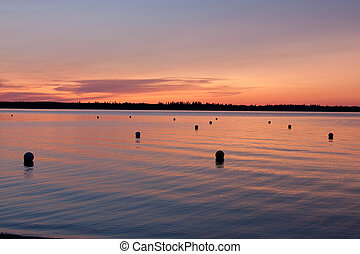 Sunset with Buoys on Water - A warm glowing sunset on a...