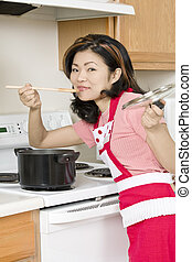 Asian Woman - Beautiful Asian woman cooking a large pot of...