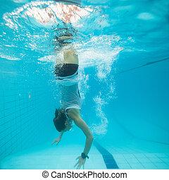 Underwater in a pool - Woman freediving underwater in a pool