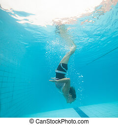 Underwater in a pool - Woman freediving underwater in a pool