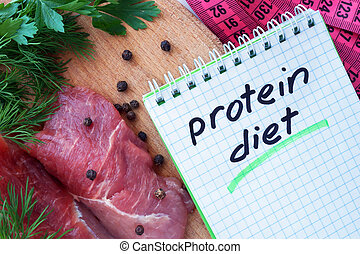 Notepad with protein diet and fresh meat  on wooden board