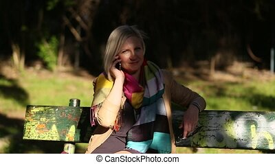 Young woman talking on mobile phone sitting on a park sunlit...