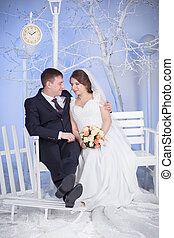the bride and groom sit on the bench - Pregnant bride and...